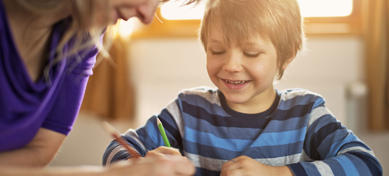 Boy getting homework help from his mother